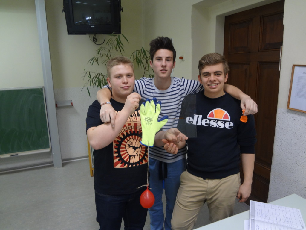 Saugnapfhandschuh hält an einer Glasscheibe. Im Hintergrund (v.l.n.r): Michael, Justus, Valentin
